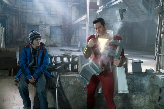 """A supersized Billy Batson (Zachary Levi) tests his might as his foster brother Freddy (Jack Dylan Grazer) looks on in """"Shazam!"""""""