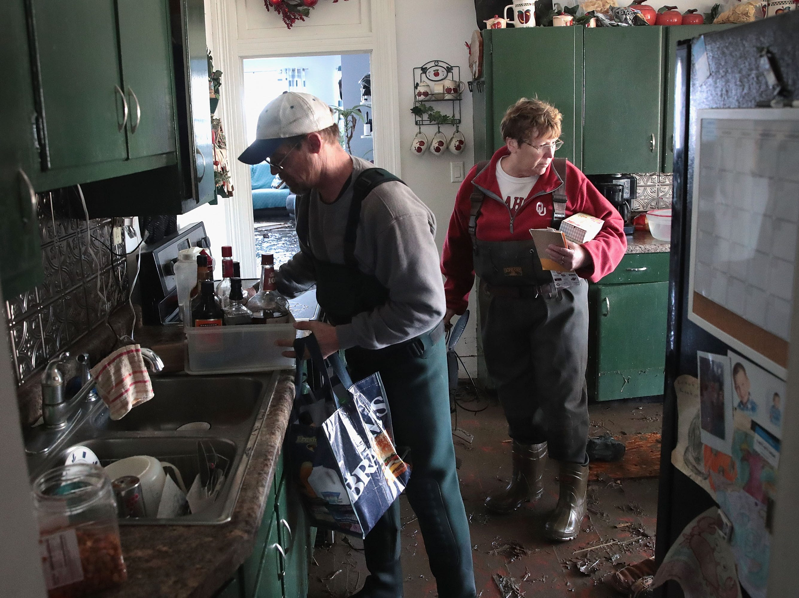 Bill Peeler helps his friend Kathy Drummond remove items from her flooded home on March 20, 2019 in Hamburg, Iowa.