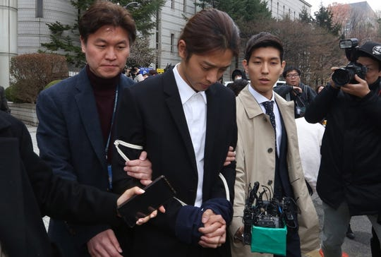 South Korean K-pop star Jung Joon-young, center, walks with policemen while waiting for the court's decision at the Seoul District Court in Seoul, South Korea, on March 21, 2019. The pop star was at court to attend a hearing after he admitted to secretly filming himself engaging in sexual activities with ten or more women and sharing the footage.