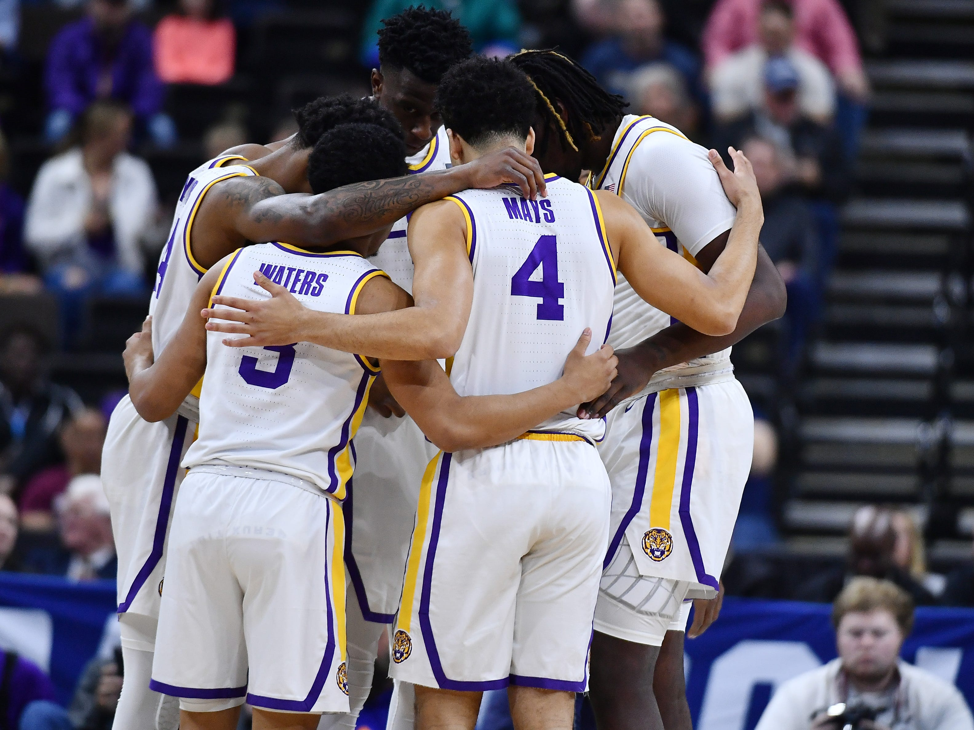 First round: LSU Tigers players, playing without suspended head coach Will Wade, huddle up during their win over the Yale Bulldogs.