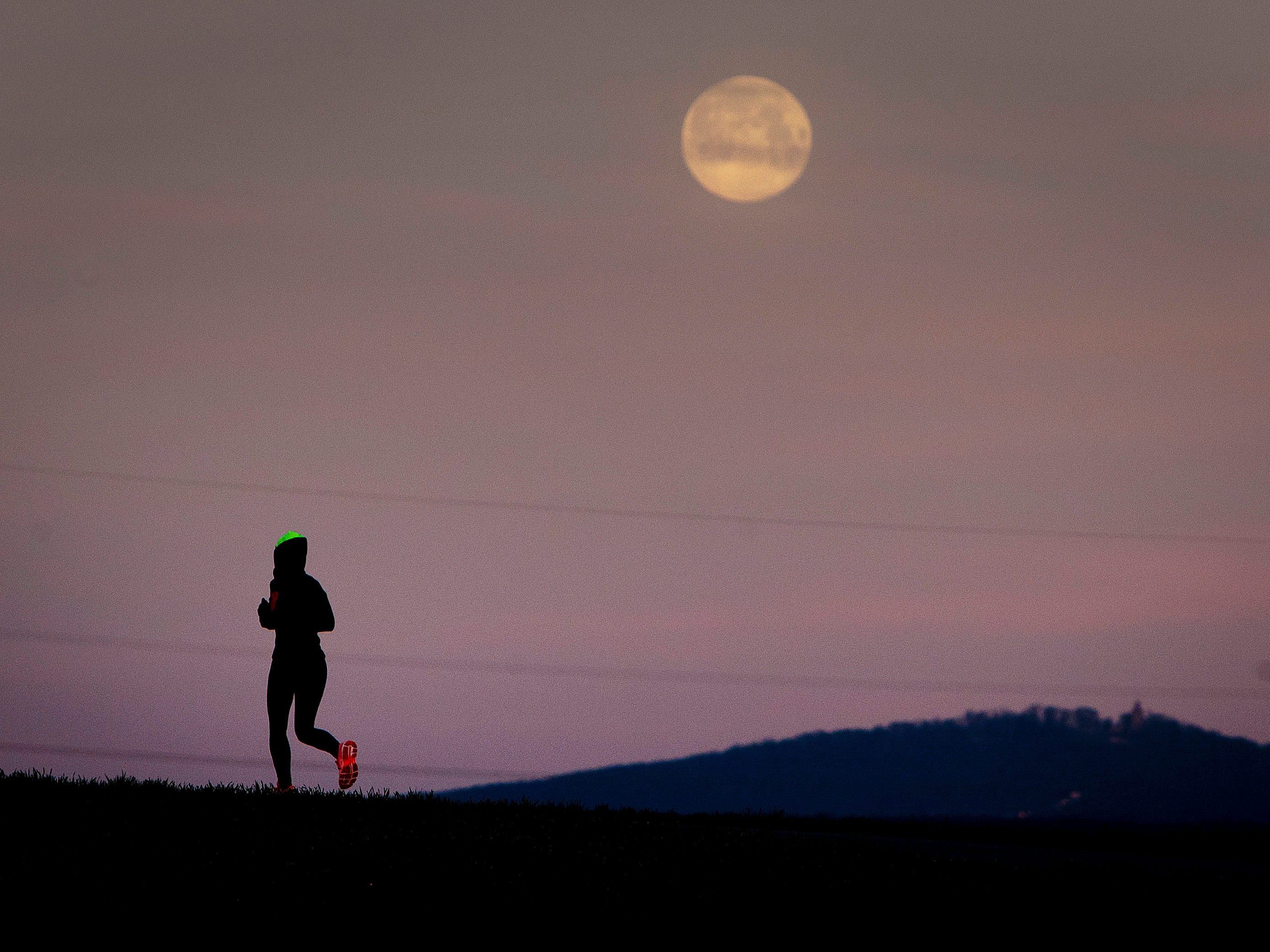 A woman runs on a small road between fields and acres just before the moon sets in Frankfurt, Germany, Thursday, March 21, 2019. (AP Photo/Michael Probst) ORG XMIT: PFRA105