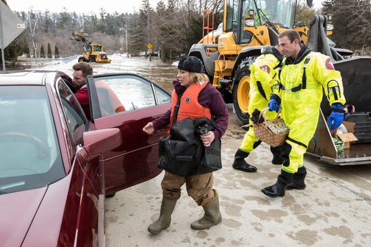 Annette Soukup loads her dog and belongings into her car with help from firefighter Kevin Fabian after being evacuated from her residence because of flooding on the Manitowoc River on March 21, 2019, in Wisconsin.