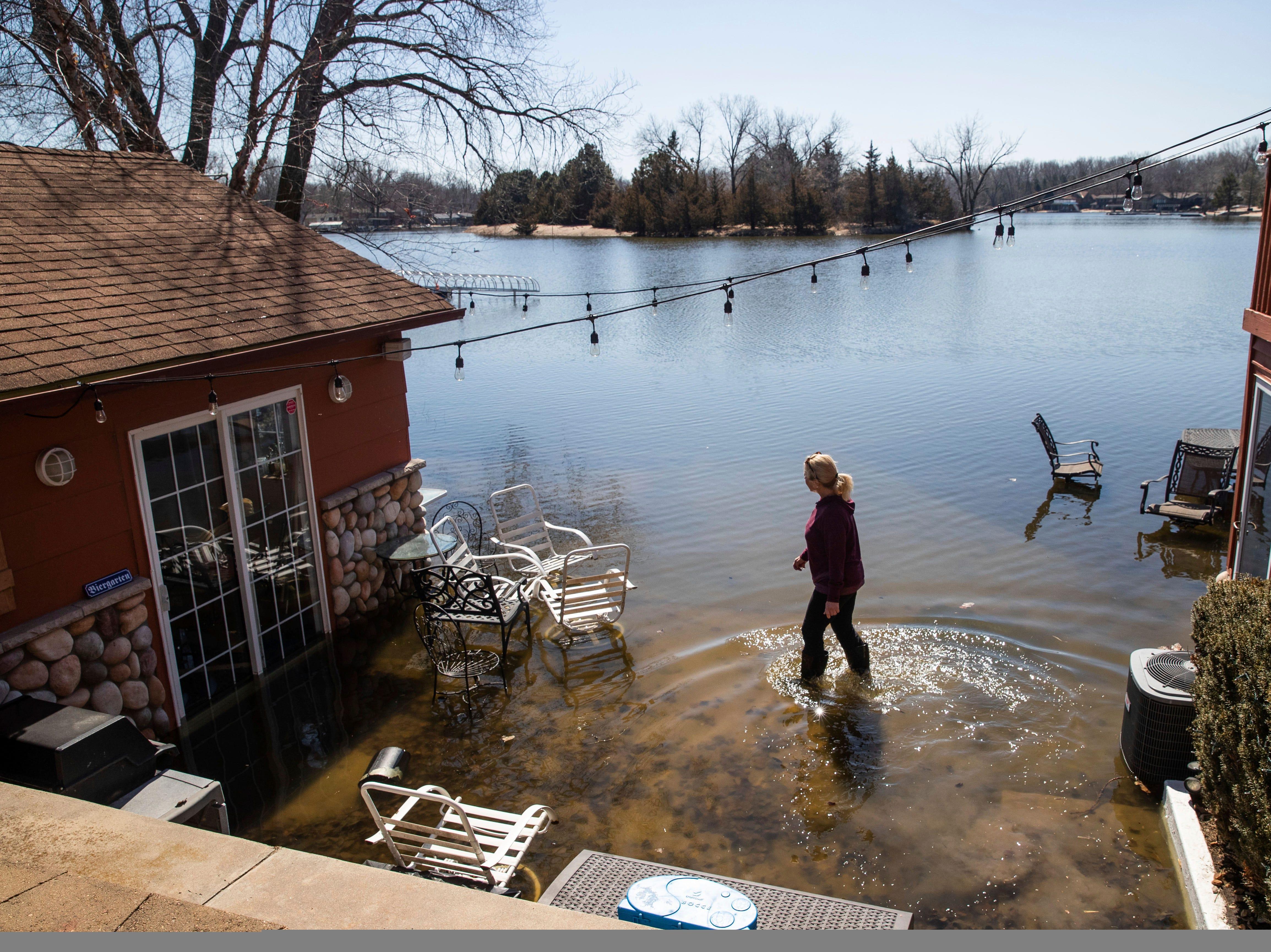 Lori Steinauer walks through a patio area at her flooded cabin Thursday, March 21, 2019, in Ashland, Neb.