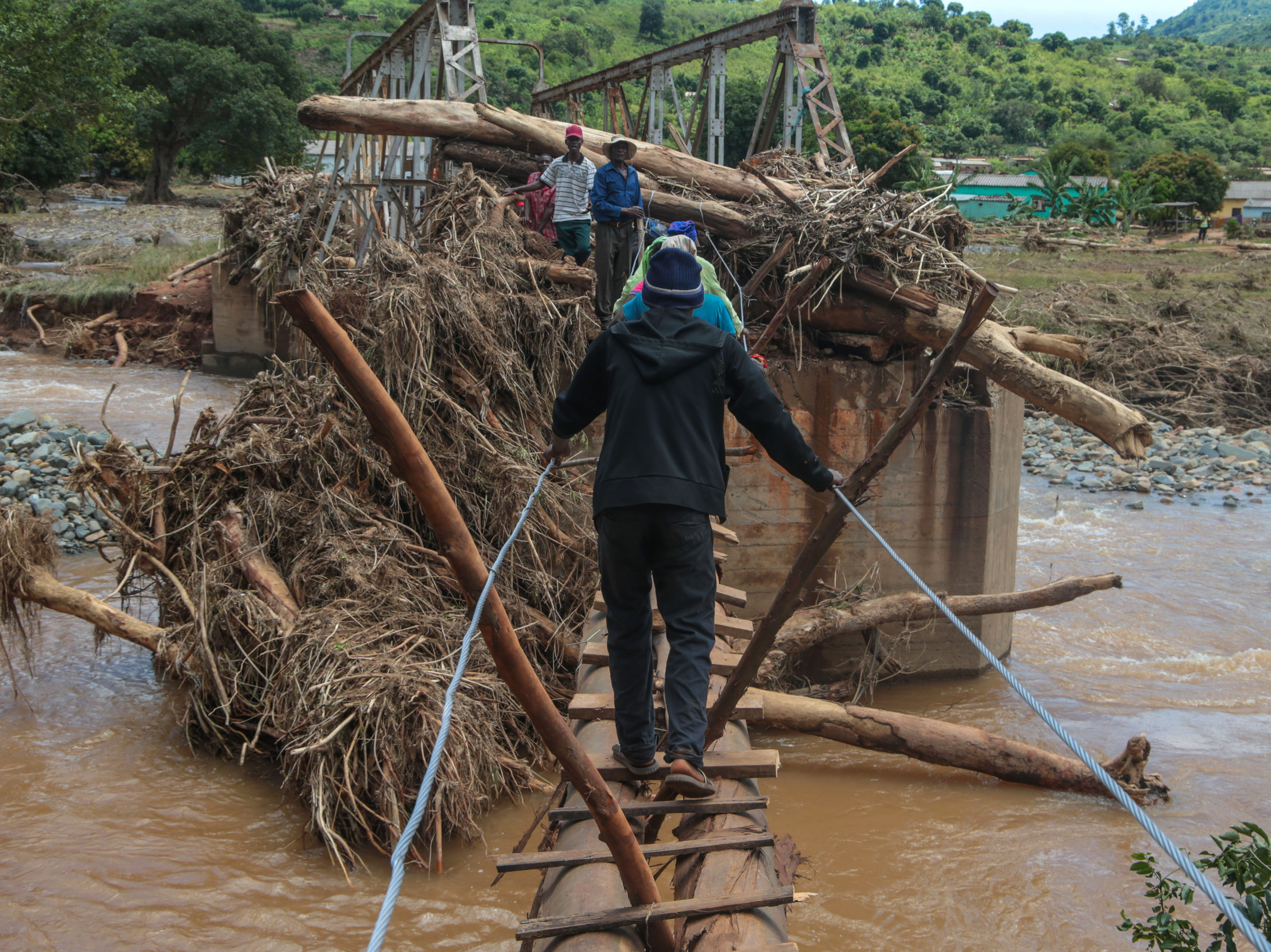 Civilians cross a makeshift bridge over a river that surged days earlier during Cyclone Idai in Chipinge, Zimbabwe.