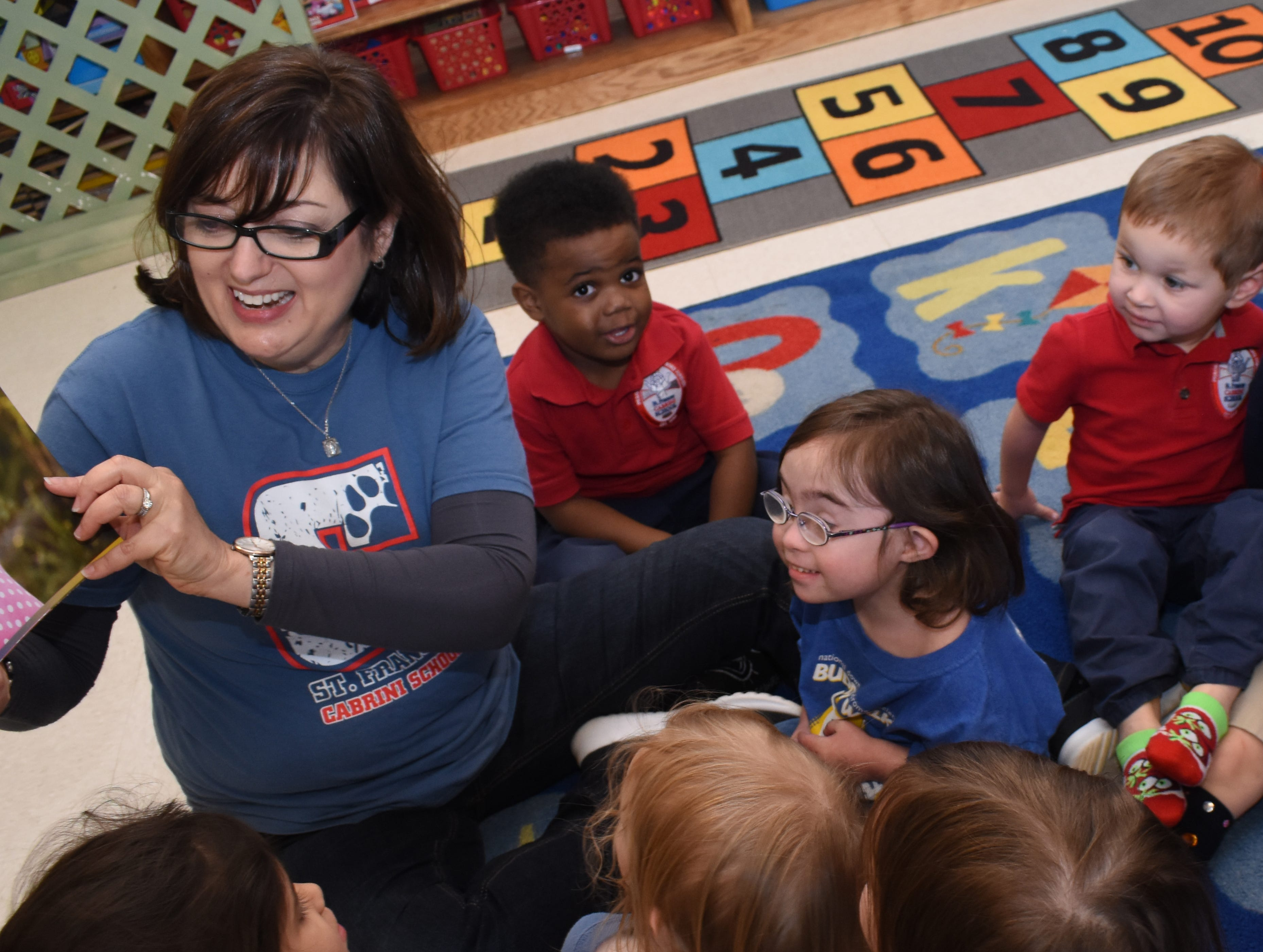 """Students at St. Frances Cabrini School celebrated World Down Syndrome Day Thursday, March 21, 2019. """"Rock Your Socks"""" was the theme for the day. For $2 students could wear crazy socks with jeans and a spirit shirt. Gail Callahan (left), a pre-Kindergarten three teacher, read a book to her class written by another Cabrini teacher Ashley Distefano, titled """"The Upside of Downs."""" The book was written for Distefano's daughter Elizabeth Butler, 4 (right, in blue), a student of Callahan's, who has Down syndrome. The book also features another Cabrini student who has Down, Sydney Rud, 4,whose photo is shown in the book."""
