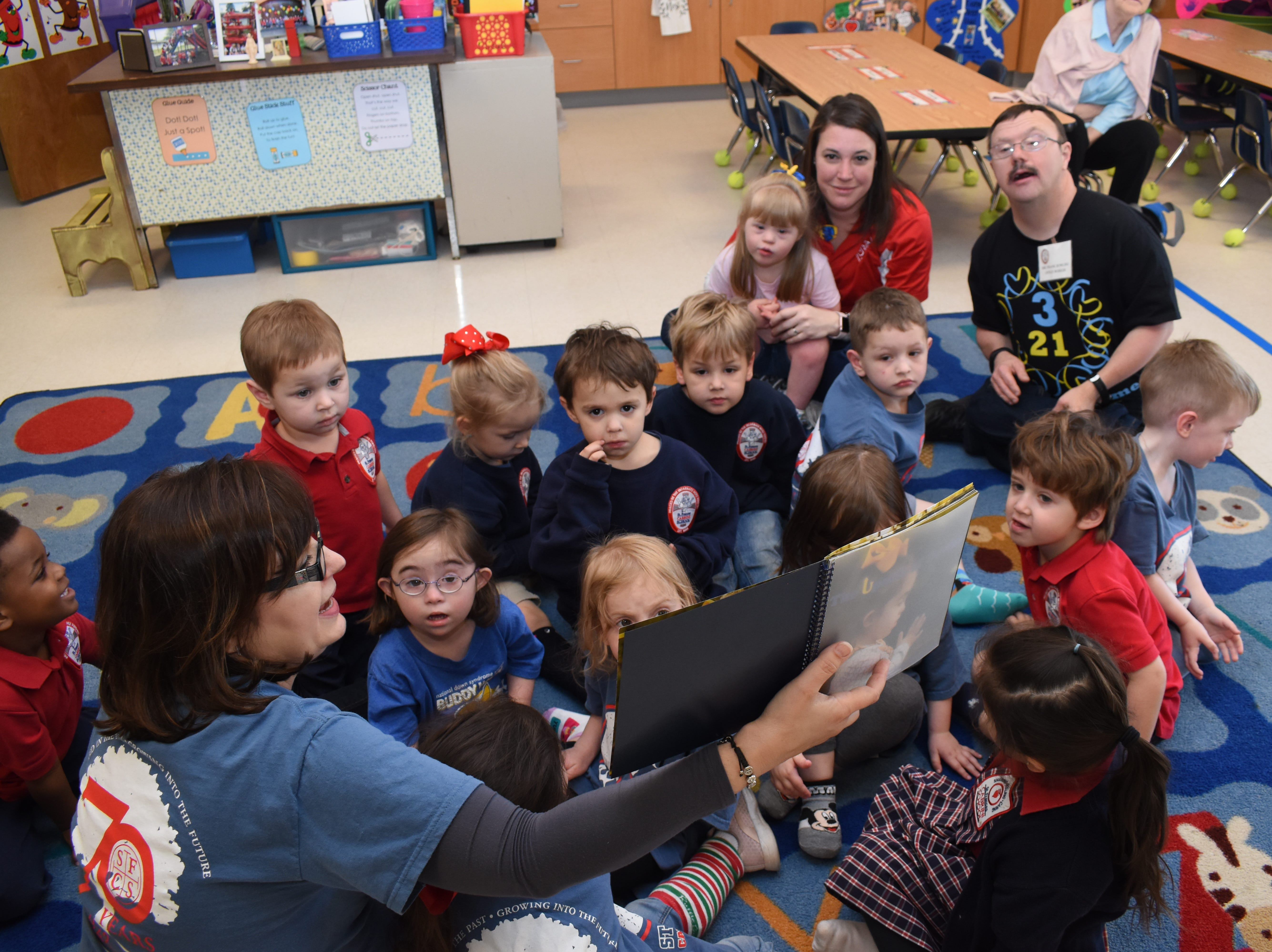 """Students at St. Frances Cabrini School celebrated World Down Syndrome Day Thursday, March 21, 2019. """"Rock Your Socks"""" was the theme for the day. For $2 students could wear crazy socks with jeans and a spirit shirt. Gail Callahan (lower left), a pre-Kindergarten three teacher, read a book to her class written by another Cabrini teacher Ashley Distefano, titled """"The Upside of Downs."""" The book was written for Distefano's daughter Elizabeth Butler, 4 (second from Callahan), who has Down syndrome. The book also features another Cabrini Student who has Down, Sydney Rud, 4."""