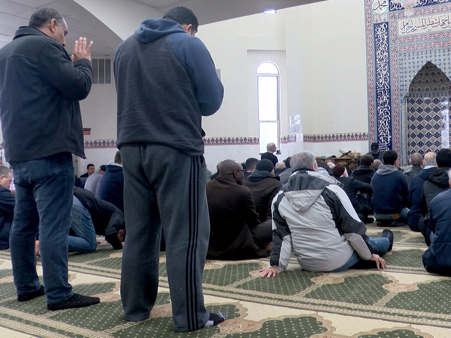 Men pray at Masjid Al-Aman in Middletown Friday, March 22, 2019.  Community members formed a ring around the mosque while the service went on inside.