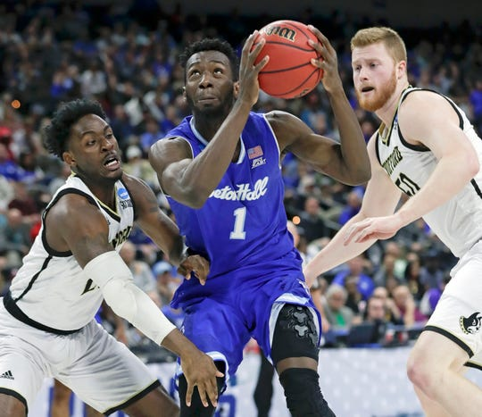 Seton Hall's Michael Nzei (1) looks for a shot as he gets between Wofford's Tray Hollowell, left, and Matthew Pegram