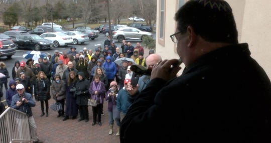 Rabbi Laurence Malinger, of Temple Shalom in Aberdeen, blows a shofar before community members formed a ring around Masjid Al-Aman in Middletown during afternoon prayers Friday, March 22, 2019.