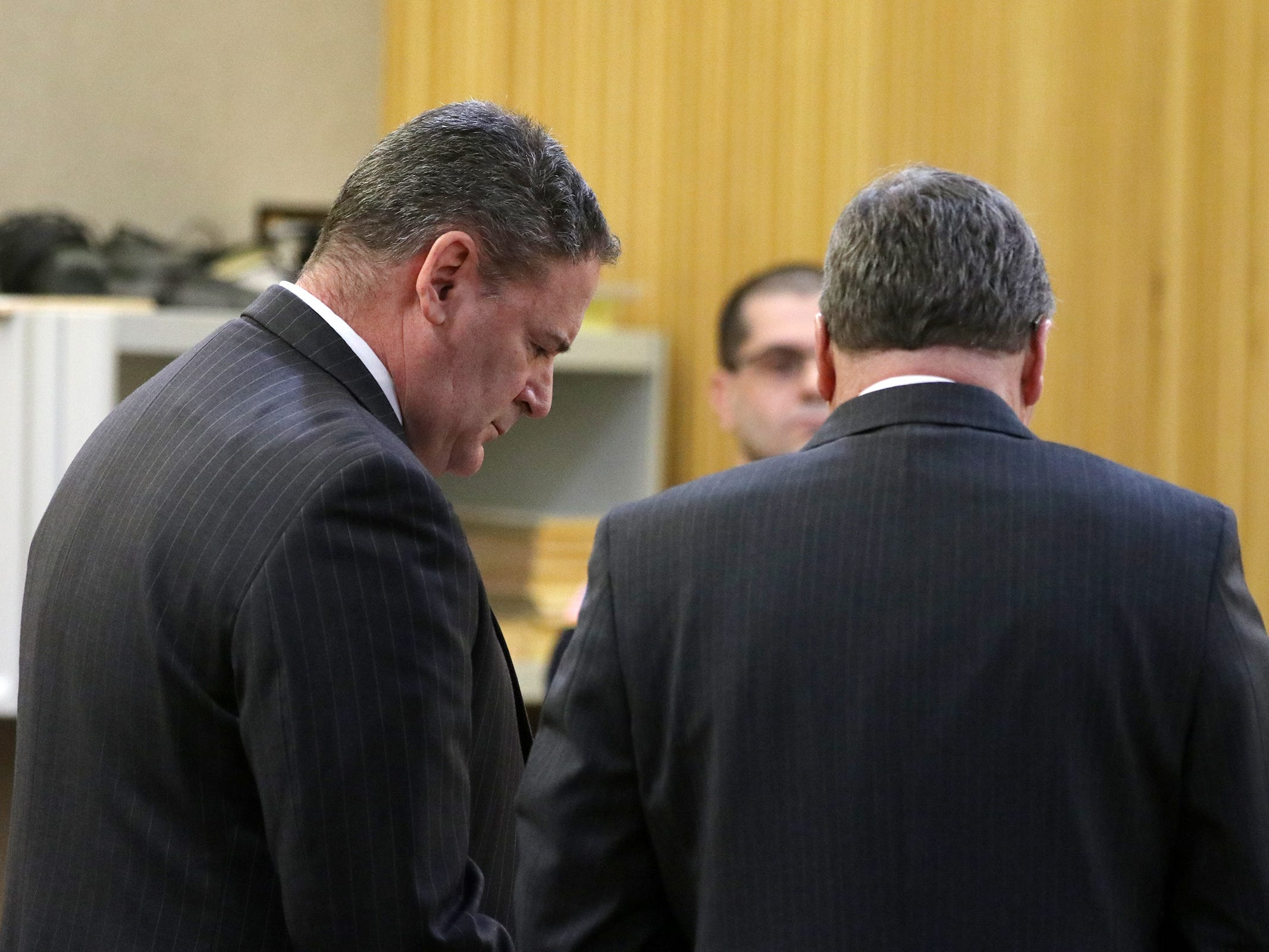 Peter Pflug of Freehold, former chief financial officer for new Horizons in Autism, for stealing almost $115,000 from the non-profit organization, speaks to his lawyer, Robert A. Honecker Jr. during sentencing before Judge Ellen Torregrossa-O'Connor at Monmouth County Courthouse in Freehold, NJ Friday, March 22, 2019.