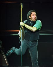 Bruce Springsteen kicks up his foot as he performs with the E Street Band during a rehearsal benefit concert at the Asbury Park Convention Center in Asbury Park, N.J., Thursday, March 18, 1999. The concert was the first time the band, which begins a world tour in Spain in April, has performed publicly together in over a decade. (AP Photo/Daniel Hulshizer)