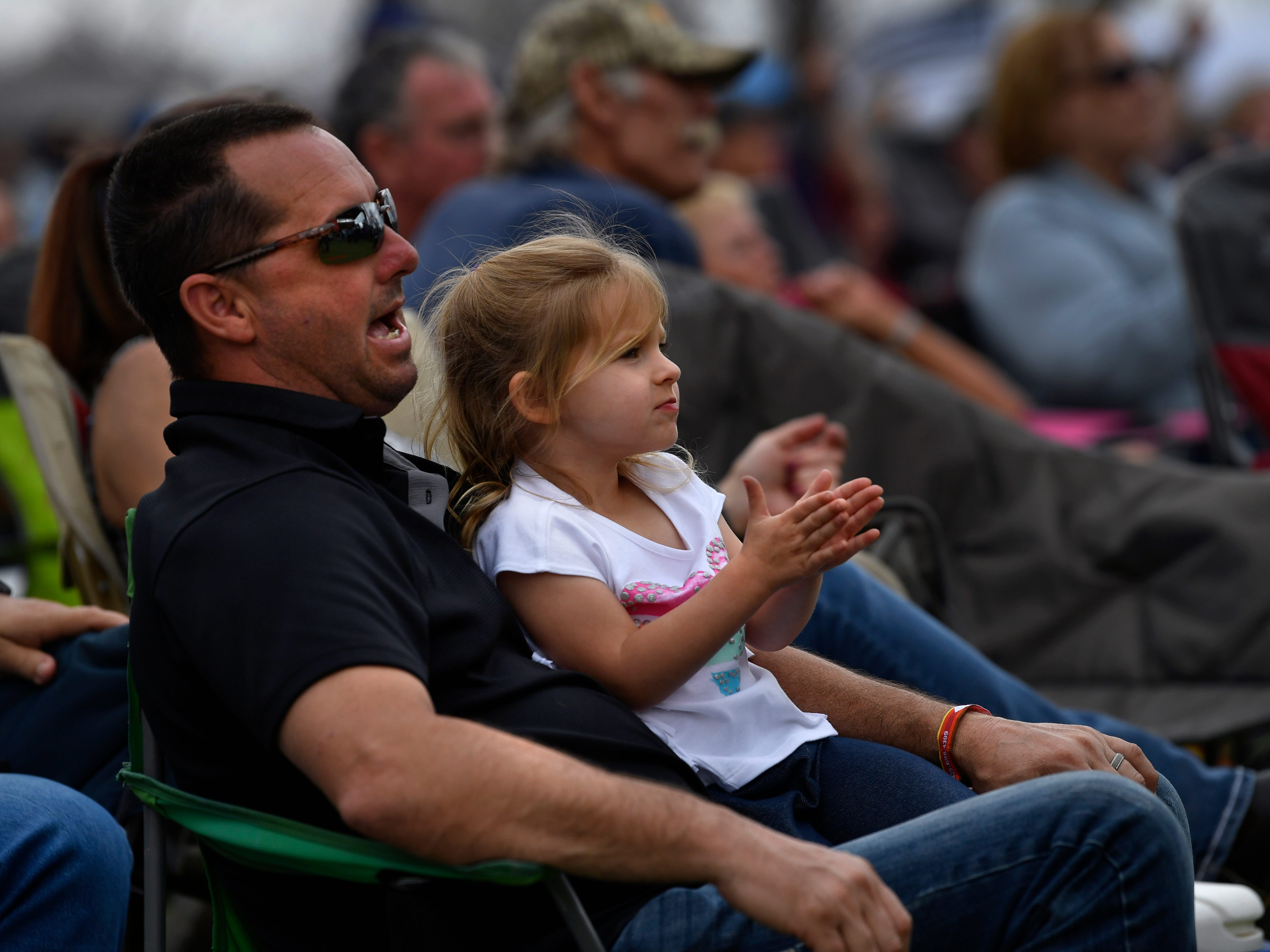 Shawn Bean watches the Jerrod Medulla Band with his four-year-old daughter Kyler on his lap during Friday's Outlaws & Legends music festival March 22, 2019.