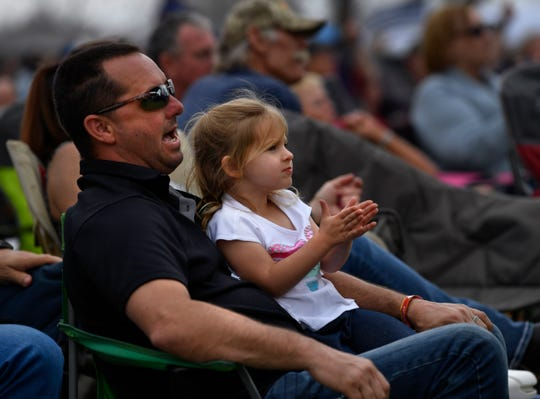 Shawn Bean watches the Jerrod Medulla Band with his 4-year-old daughter Kyler on his lap at the start of this weekend's Outlaws & Legends Music Festival on Friday afternoon.