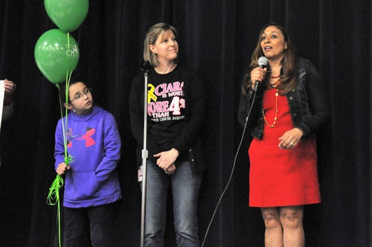 Ward Elementary third-grade teacher Laurie Velasquez, center, listens as Maria McLendon, right, director of brand strategy for National Life Group, describes student Ciara Husing's nomination of Velasquez for the company's Life Changer of the Year Award during a school assembly Friday.