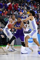Abilene Christian forward Jaren Lewis (1) dribbles the ball as Kentucky forward Reid Travis (22) defends during the first half of their NCAA Tournament first-round game March 21 in Jacksonville, Fla. (John David Mercer-USA TODAY Sports)