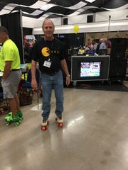 Lou Zientek, CEO of Communities of Abilene Federal Credit Union, skates in a Pac-Man t-shirt during a 1980s-themed Business Expo in 2017.