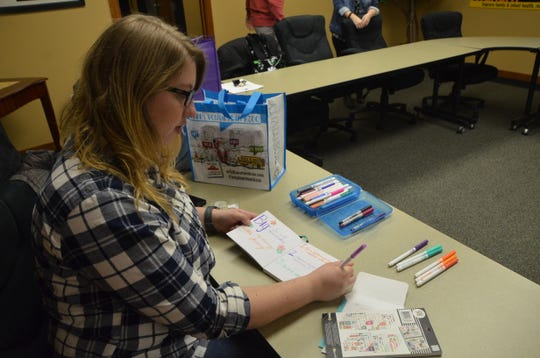 Sarah Mead (pictured) prepares materials for a scrapbook she has been working on with her Little as part of the Big Brothers Big Sisters Bigs in Business program.