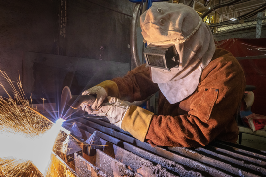Katherine LaPierre, of Belfair, cuts a piece of metal March 14 inside Building 460 at Puget Sound Naval Shipyard and Intermediate Maintenance Facility.