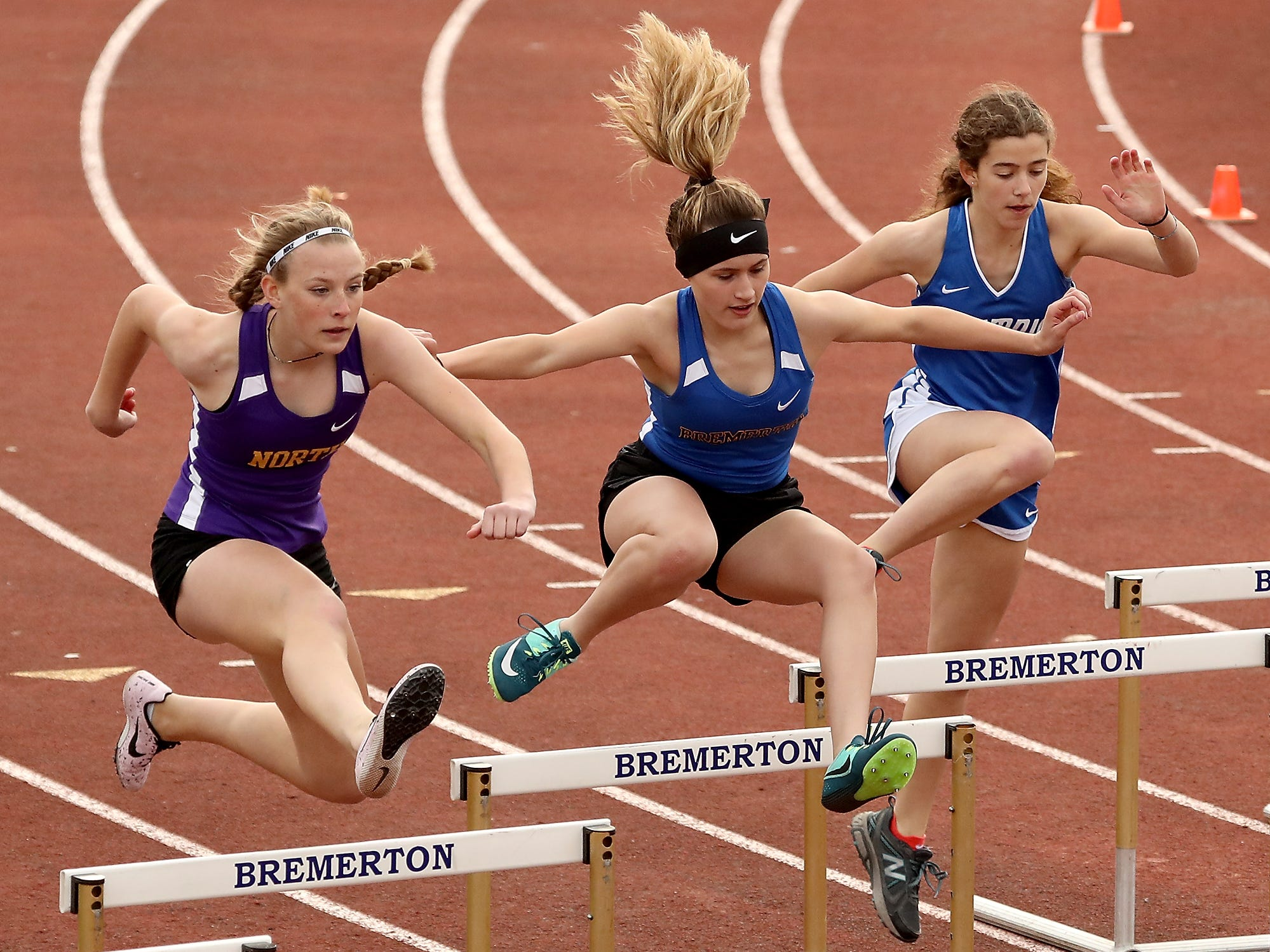 Competitors in the 300 Meter Hurdles (left to right) North Kitsap's Kaiya Ochs, Bremerton's Cecilia Souza and Olympic's Olivia McFall soar over the hurdles during the meet at Bremerton High on Thursday, March 21, 2019.