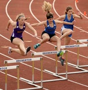 North Kitsap's Kaiya Ochs (left to right), Bremerton's Cecilia Souza and Olympic's Olivia McFall leap over the hurdles during the meet at Bremerton High on Thursday, March 21.