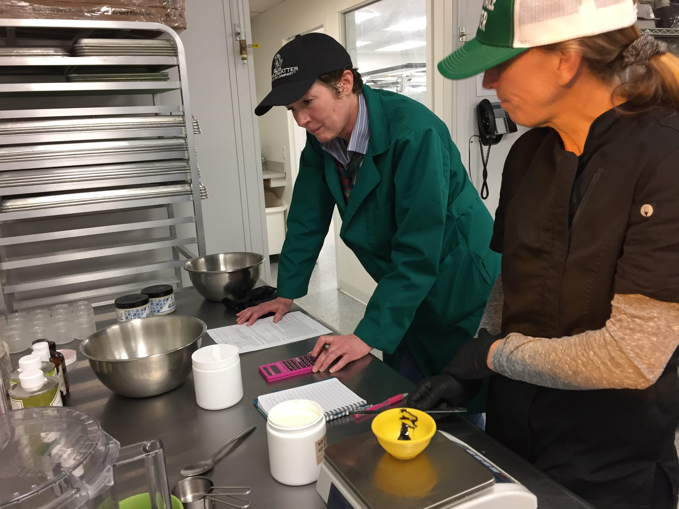 Bridget Conry, left, director of marketing at CVD, Inc., works with Amy Bacon to develop a recipe for a new CBD-infused shea butter scrub in the commercial kitchen at the production facility.