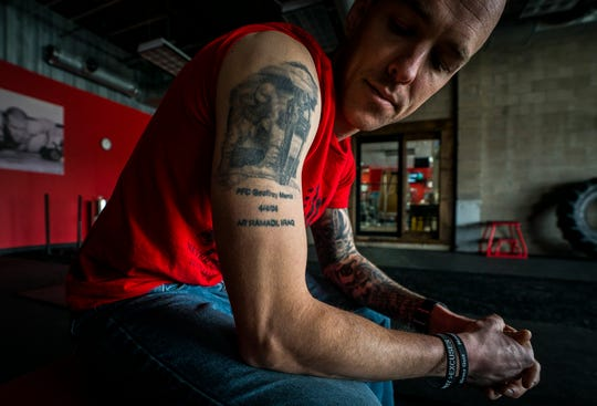 U.S. Marine Veteran Jason Mosel of Corinth, Vt., looks down at his right arm and the tattoo honoring his friend and fellow Marine Geoffrey Morris who was killed in action in Iraq in 2004. The memory of the day Morris was killed, and others from Mosel's three deployments, nearly drove him to suicide. On Friday night, March 22, 2019, Mosel will try to set a new Guinness World Record for the most burpees performed in 12 hours to honor his friend and raise awareness about solider and veteran suicides.