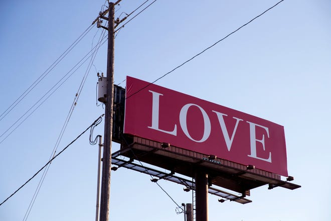"""A red billboard with the word """"LOVE"""" on it can be seen along State Highway 358 near Agnes Street as a part of the international """"Love on Every Billboard"""" movement. Jamie Rae Hellen, a travel nurse in Corpus Christi, raised funds with her friends to bring a """"LOVE"""" billboard to the city."""