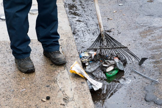 A code enforcement official rakes up trash on a block in East Camden Friday, March 22, 2019.