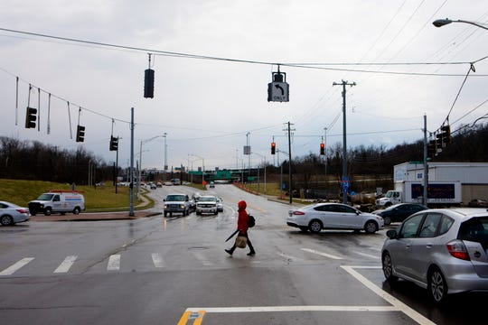 A pedestrian crosses the street at the intersection of Virginia and Colerain avenues on Thursday, March 22, 2019, in Cincinnati. According to the Ohio Department of Transportation, that is one of the most dangerous intersections in the state.