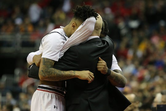 Cincinnati Bearcats senior guard Cane Broome (15) and Cincinnati Bearcats senior guard Justin Jenifer (3) are embraced by Cincinnati Bearcats head coach Mick Cronin in the final moments of the second half of the NCAA Tournament Round of 64 game, Friday, March 22, 2019, at Nationwide Arena in Columbus, Ohio. Cincinnati Bearcats lost to the Iowa Hawkeyes 79-72.