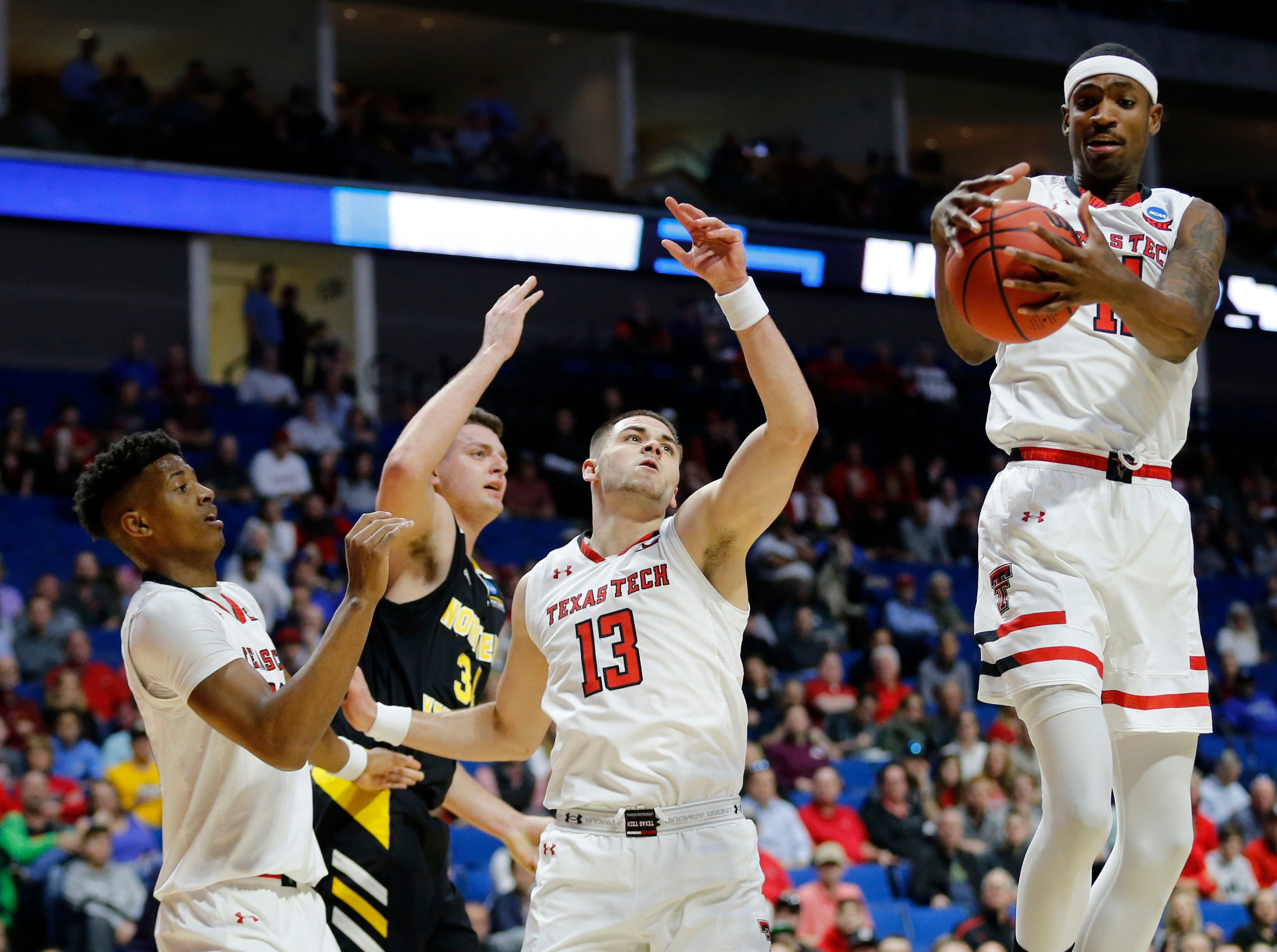Texas Tech Red Raiders forward Tariq Owens (11) pulls down a rebound over Northern Kentucky Norse forward Drew McDonald (34) in the first half of the NCAA Tournament First Round game between the 14-seeded Northern Kentucky Norse and the 3-seeded Texas Tech Red Raiders the BOK Center in downtown Tulsa on Friday, March 22, 2019. Texas Tech led 30-26 at halftime.