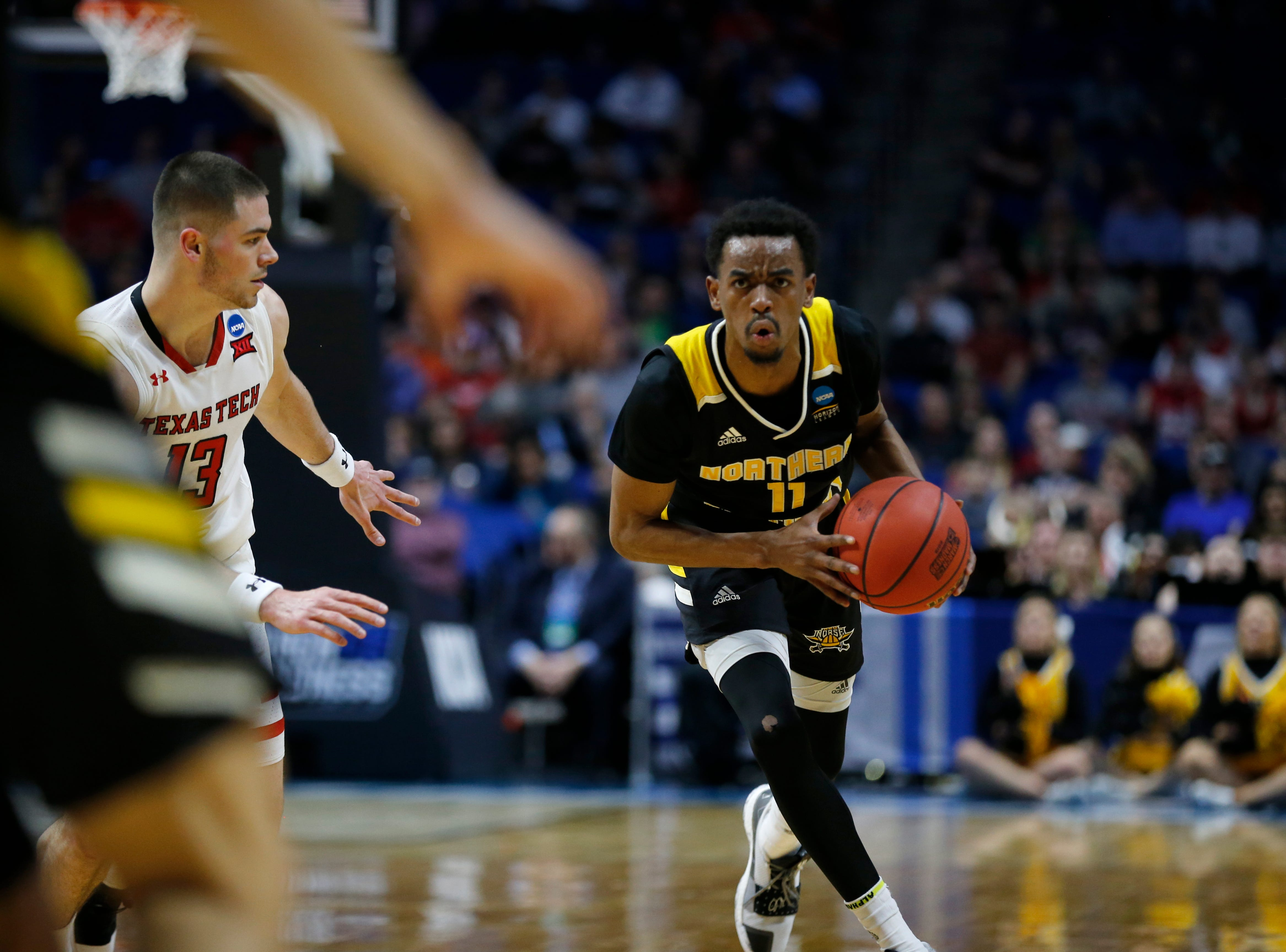 Northern Kentucky Norse guard Jalen Tate (11) looks to make a pass under pressure from Texas Tech Red Raiders guard Matt Mooney (13) in the first half of the NCAA Tournament First Round game between the 14-seeded Northern Kentucky Norse and the 3-seeded Texas Tech Red Raiders the BOK Center in downtown Tulsa on Friday, March 22, 2019. Texas Tech led 30-26 at halftime.