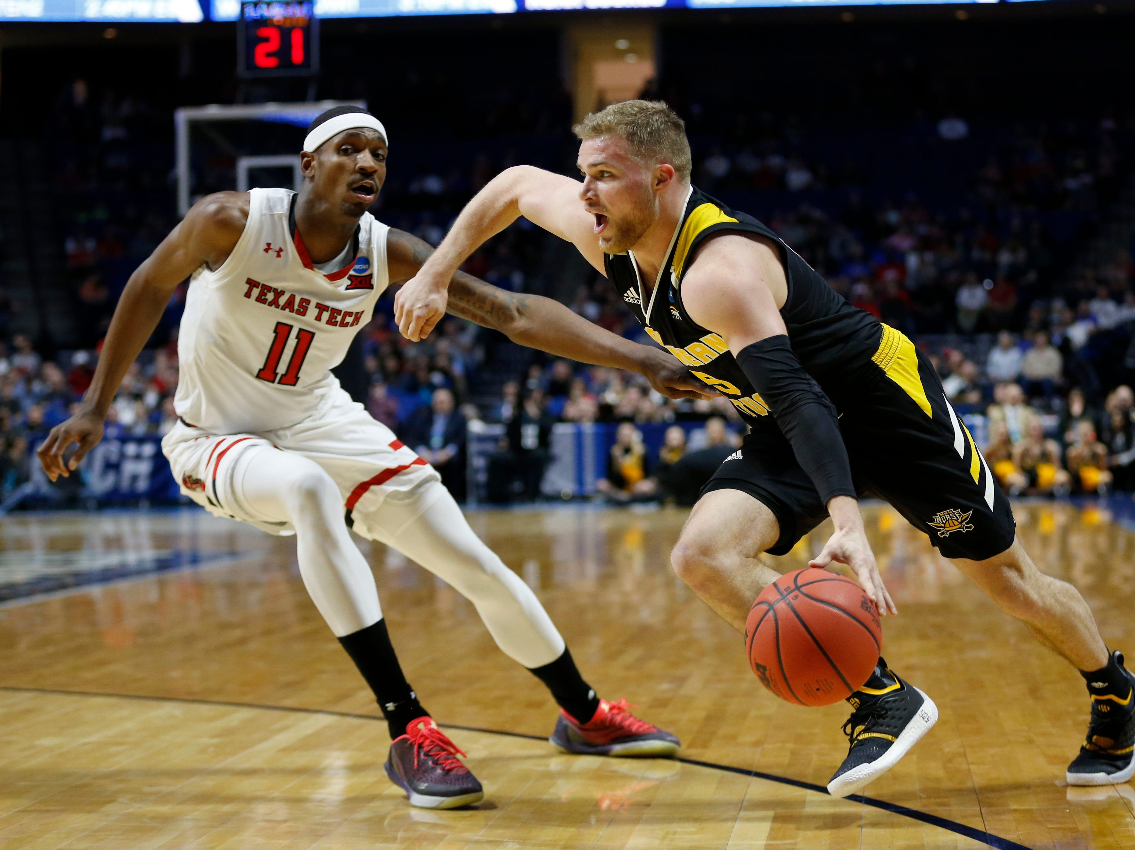 Northern Kentucky Norse guard Tyler Sharpe (15) drives against Texas Tech Red Raiders forward Tariq Owens (11) in the first half of the NCAA Tournament First Round game between the 14-seeded Northern Kentucky Norse and the 3-seeded Texas Tech Red Raiders the BOK Center in downtown Tulsa on Friday, March 22, 2019. Texas Tech led 30-26 at halftime.