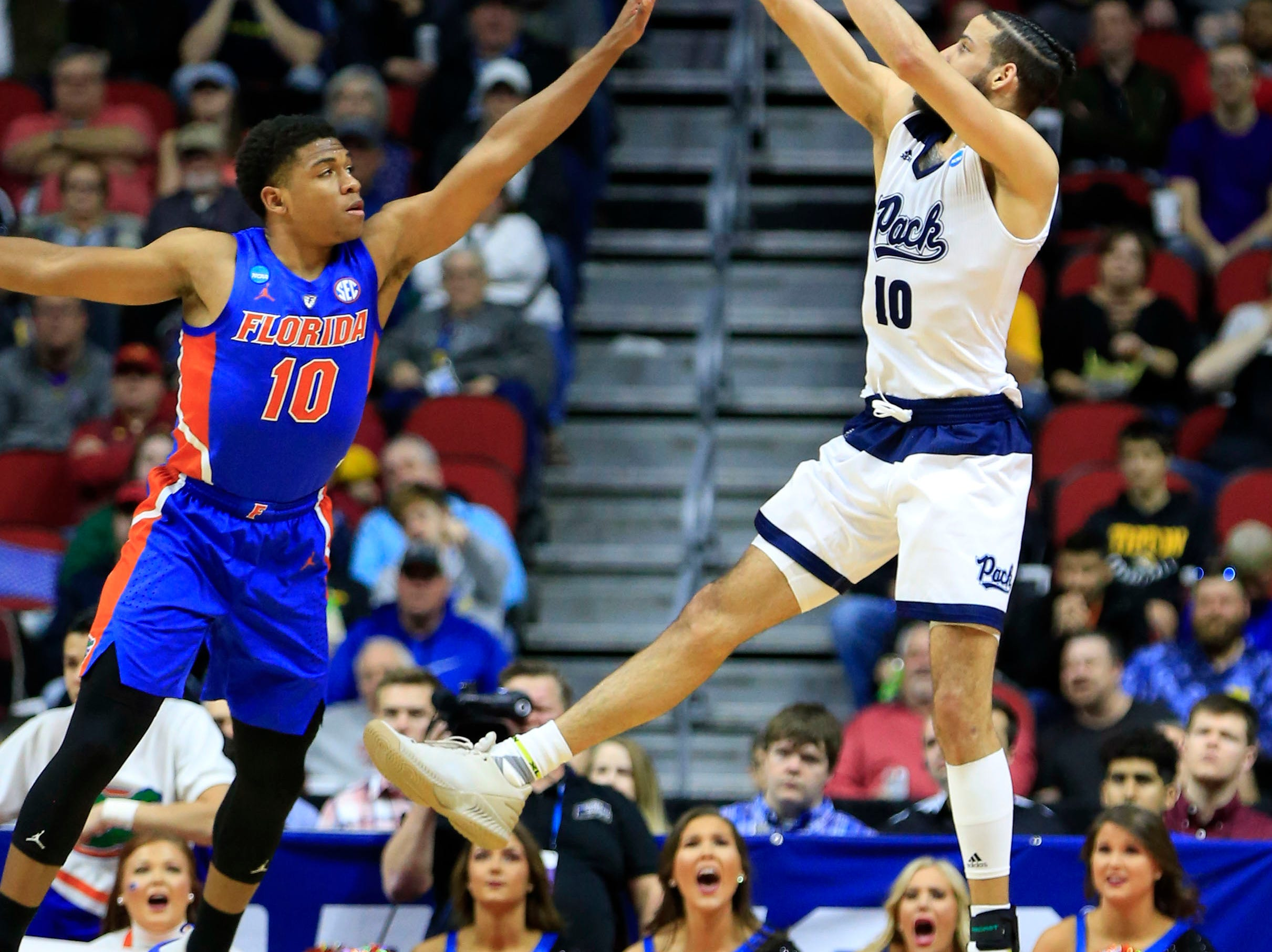Nevada forward Caleb Martin puts up a shot as Florida guard Noah Locke defends during their NCAA Division I Men's Basketball Championship First Round game on Thursday, March 21, 2019 in Des Moines.