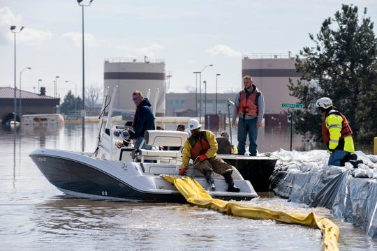 In this March 18, 2019, photo released by the U.S. Air Force, environmental restoration employees deploy a containment boom from a boat on Offutt Air Force Base in Nebraska, as a precautionary measure for possible fuel leaks in the flooded area. Surging unexpectedly strong and up to 7 feet high, the Missouri River floodwaters that poured on to much the Nebraska air base that houses the U.S. Strategic Command overwhelmed the frantic sandbagging by troops and their scramble to save sensitive equipment, munitions and aircraft.