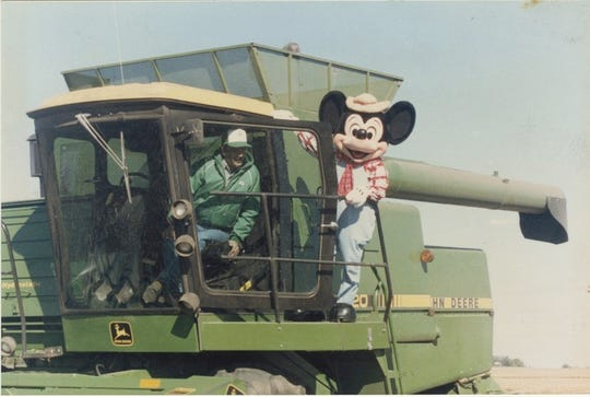 """Mickey Mouse joined Joe Pitzenberger in combining corn from a field near Dougherty, Iowa, in the fall of 1988. The Pitzenbergers were commissioned that year by the Walt Disney Company to plant corn and oats in the shape of Mickey Mouse to honor the character's 60th birthday. The 520-acre field became a sensation as air travelers could see """"The World's Largest Field Mouse"""" from 30,000 feet."""