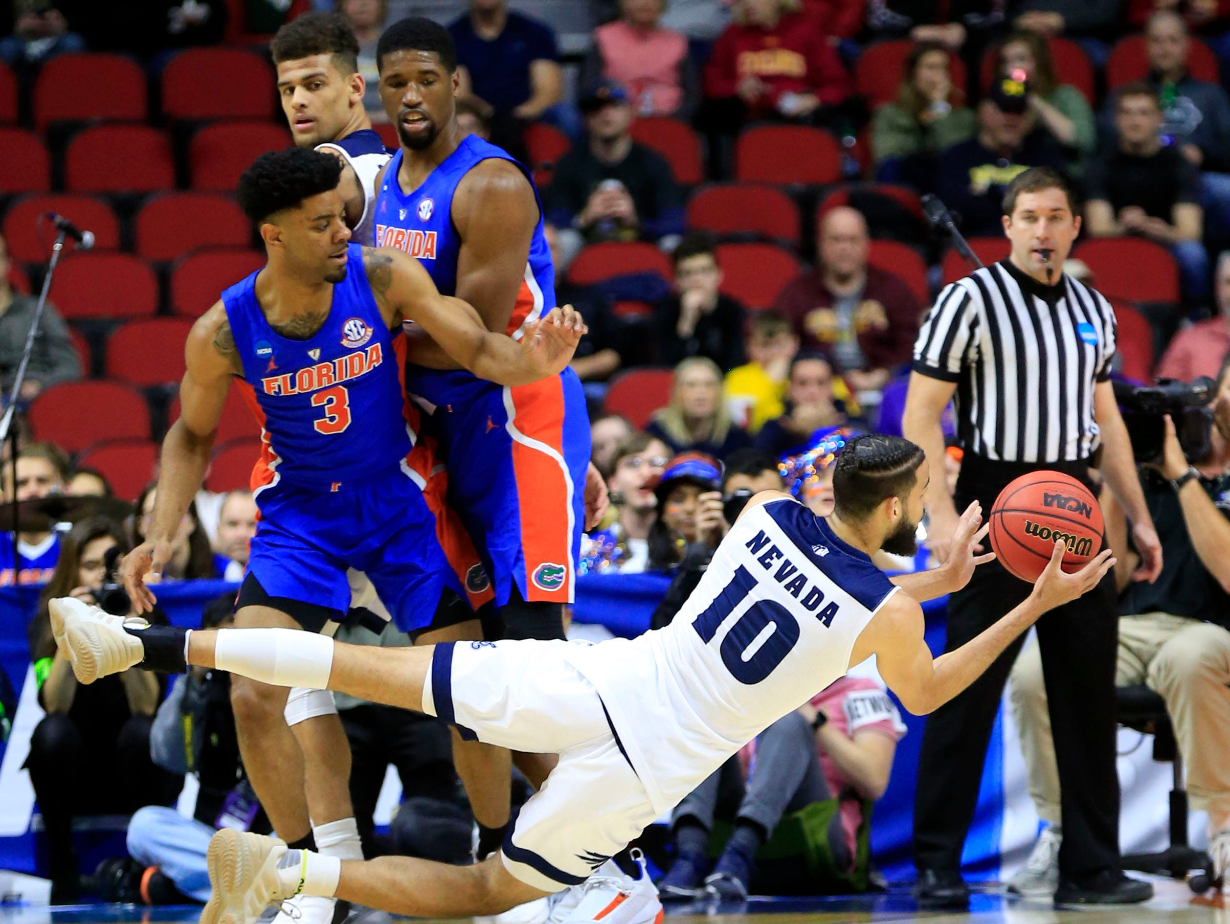 Nevada forward Caleb Martin passes as Florida guard Jalen Hudson defends during their NCAA Division I Men's Basketball Championship First Round game on Thursday, March 21, 2019 in Des Moines.