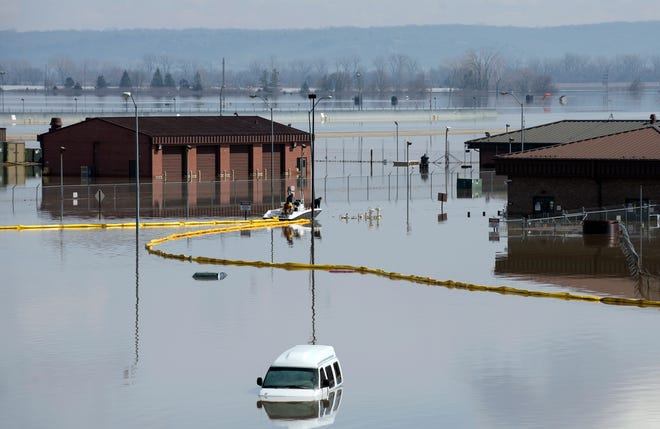 In this March 18, 2019 photo released by the U.S. Air Force, environmental restoration employees deploy a containment boom from a boat on Offutt Air Force Base in Neb., as a precautionary measure for possible fuel leaks in the flooded area. Surging unexpectedly strong and up to 7 feet high, the Missouri River floodwaters that poured on to much the Nebraska air base that houses the U.S. Strategic Command overwhelmed the frantic sandbagging by troops and their scramble to save sensitive equipment, munitions and aircraft.