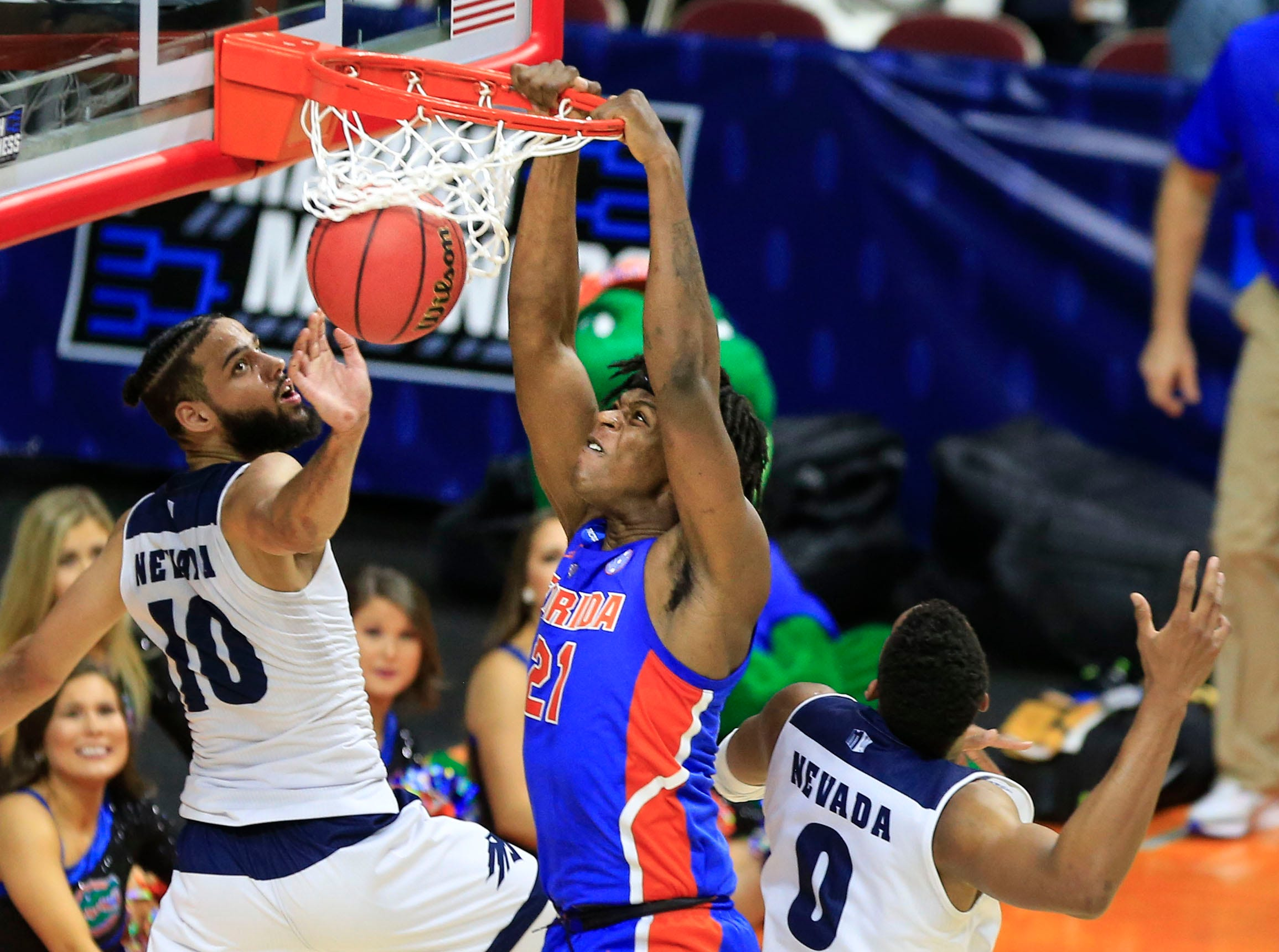 Florida forward Dontay Bassett dunks the ball as Nevada forward Caleb Martin and Nevada forward Tre'Shawn Thurman defend during their NCAA Division I Men's Basketball Championship First Round game on Thursday, March 21, 2019 in Des Moines.