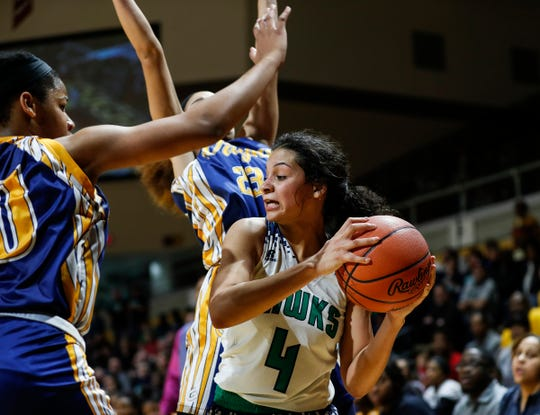 Saginaw Heritage's Moira Joiner (4) is defended by Wayne Memorial's Jeanae Terry (10) and Alana Broadnax (23) during the second half of MHSAA girls Division 1 semifinal at Van Noord Arena in Grand Rapids, Friday, March 22, 2019.