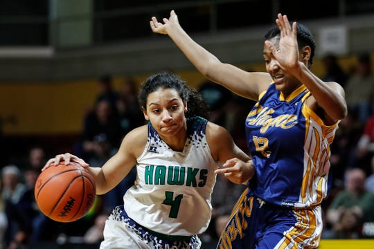 Saginaw Heritage's Moira Joiner (4) dribbles against Wayne Memorial's Jayah Hicks (12) during the MHSAA girls Division 1 semifinal at Van Noord Arena in Grand Rapids, Friday, March 22, 2019.