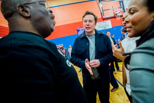 Tech billionaire Elon Musk speaks with Derrick Lopez, superintendent of Flint Community Schools, after talking to hundreds of Flint students on Friday, March 22, 2019 at Doyle-Ryder Elementary School in Flint, Mich. The Elon Musk Foundation announced in December it was giving about $424,000 to help provide laptops as the city recovers from a crisis with lead-tainted water. (Jake May/The Flint Journal via AP)