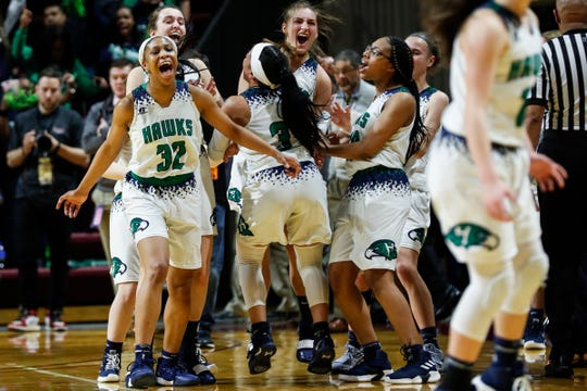 Saginaw Heritage players celebrate the Hawks' 58-55 win over Wayne Memorial during the second half of MHSAA girls Division 1 semifinal at Van Noord Arena in Grand Rapids, Friday, March 22, 2019.