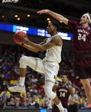 Michigan's Charles Matthews scores against Montana's Bobby Moorehead in the second half.