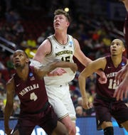 Michigan's Jon Teske towers over Montana's Sayeed Pridgett and Kendal Manuel in the NCAA tournament Thursday.