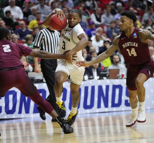 Zavier Simpson drives against Montana guards Donaven Dorsey, left, and Ahmaad Rorie during the first half.