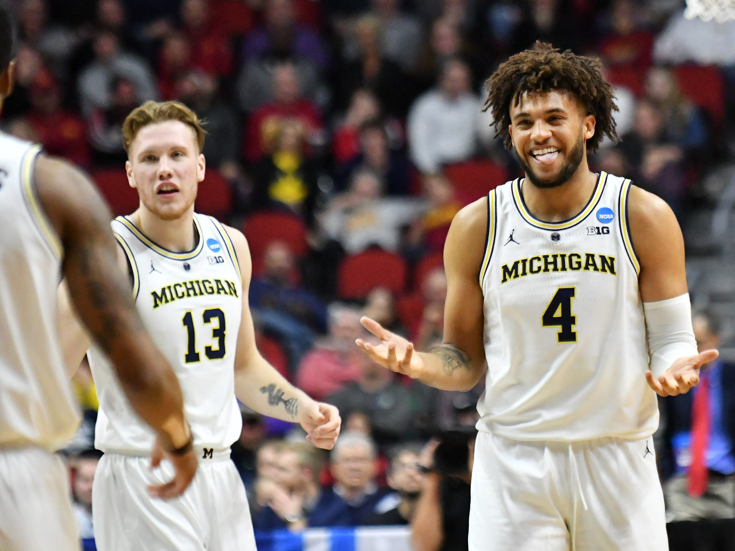 Michigan forward Isaiah Livers (4) reacts with Charles Matthews, left, at a time out in the first half.  Michigan vs Montana for Round 1 of the NCAA Tournament at Wells Fargo Arena in Des Moines, Iowa.