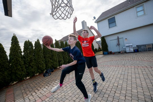 Tommy Carr and his brother, C.J., play basketball together at their home in Ann Arbor on March 13.