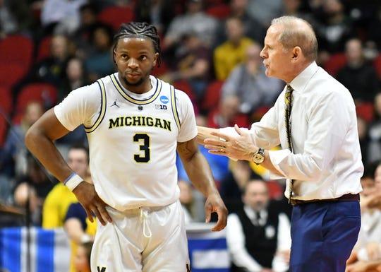 Michigan head coach John Beilein talks with Michigan guard Zavier Simpson in the first half Thursday.