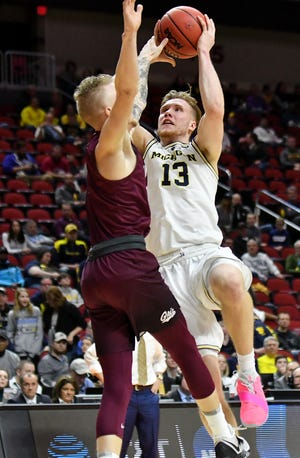 """He was a little quite guy actually,"" says Florida freshman guard Andrew Nembhard of Michigan's Ignas Brazdeikis, right. ""Always confident though, but now he shows it a little more."""